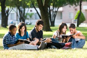 School children reading books in the grass